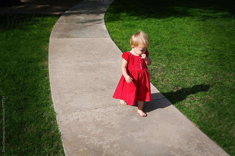 Toddler Girl In Red Dress Walking On Paved Pathway by Dina Giangregorio for Stocksy United
