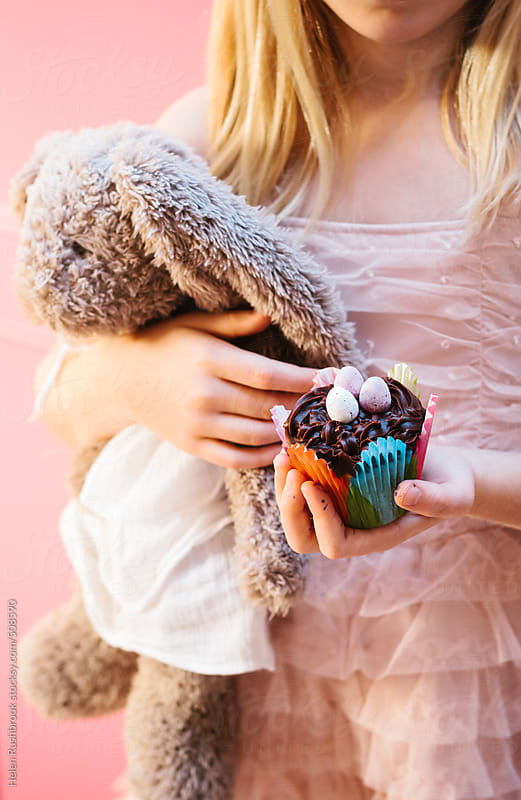 Little girl holding a cake and a toy rabbit. by Helen Rushbrook for Stocksy United
