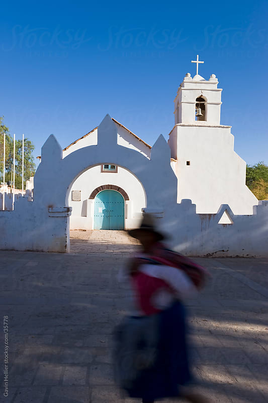 South America, Chile, Norte Grande, Atacama desert, San Pedro de Atacama, Iglesia San Pedro, Colonial adobe walled church dating from the 17th Century, local woman walking past - blurred motion by Gavin Hellier for Stocksy United