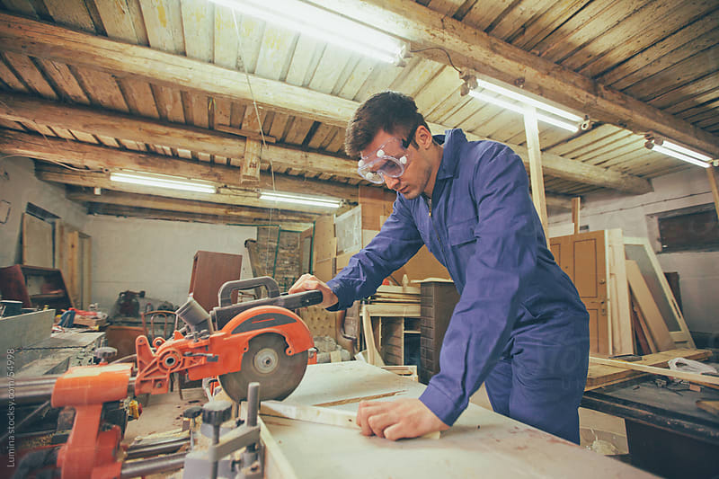 Carpenter Cutting Planks With a Circular Saw by Lumina for Stocksy United