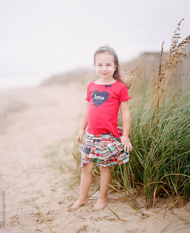 Cute young girl standing on a beach in windy weather by Jakob for Stocksy United