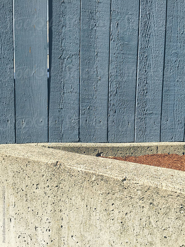 Concrete wall and painted blue fence, close up by Paul Edmondson for Stocksy United
