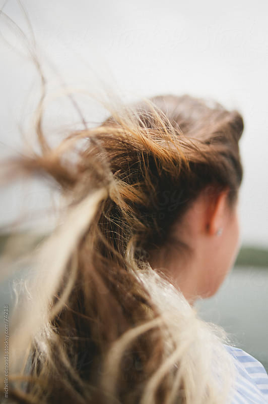 Teenaged girl on boat with wind blowing toward camera by michelle edmonds for Stocksy United