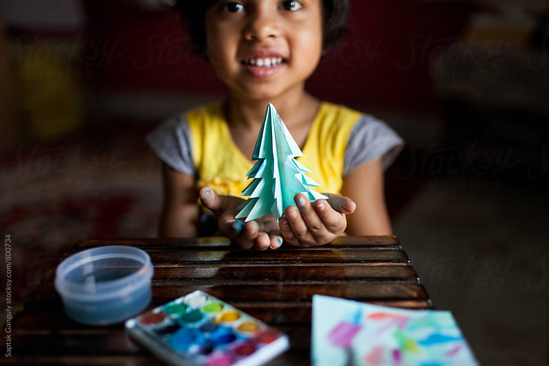 Little girl smiling with a paper Christmas tree in her hands by Saptak Ganguly for Stocksy United