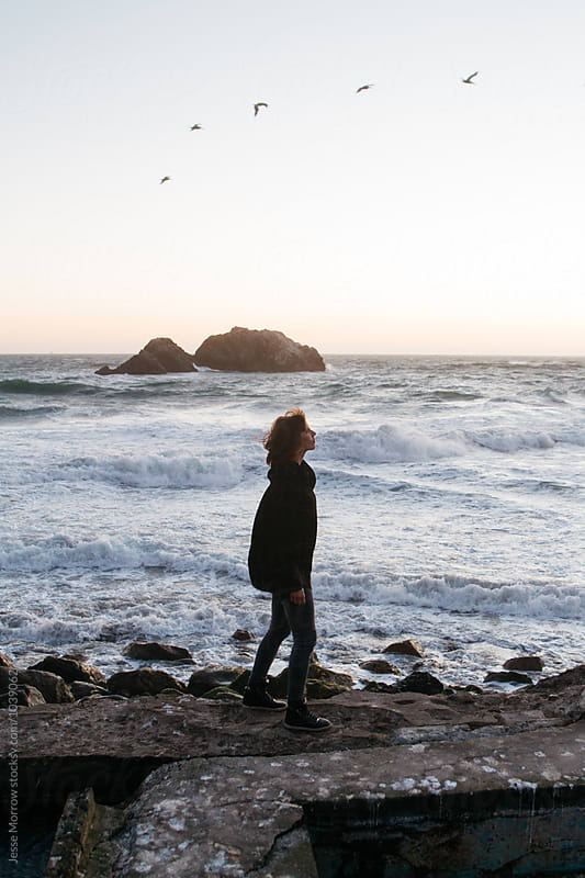 young woman walks along ocean coast during sunset while waves crash and birds fly  by Jesse Morrow for Stocksy United