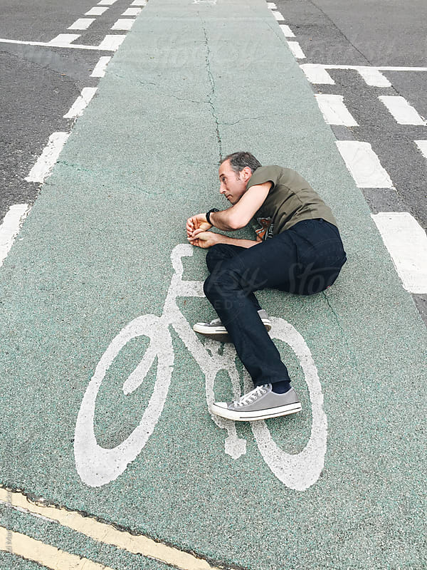 Man lying on tarmac pretending to ride a bicycle that is painted on the road by Suzi Marshall for Stocksy United