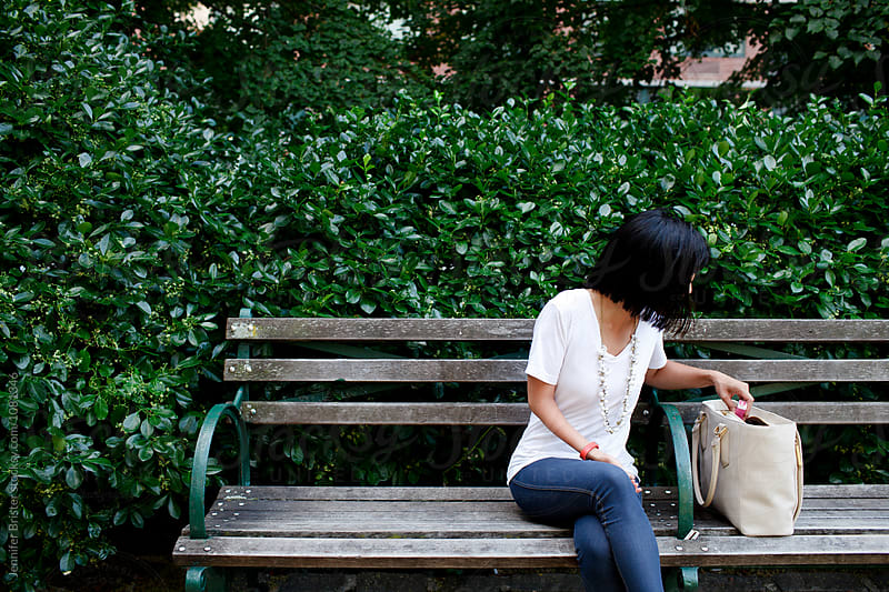 Woman sitting on park bench, looking through purse by Jennifer Brister for Stocksy United