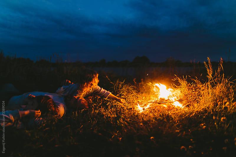 Little boy lighting a stick with the fire by Evgenij Yulkin for Stocksy United