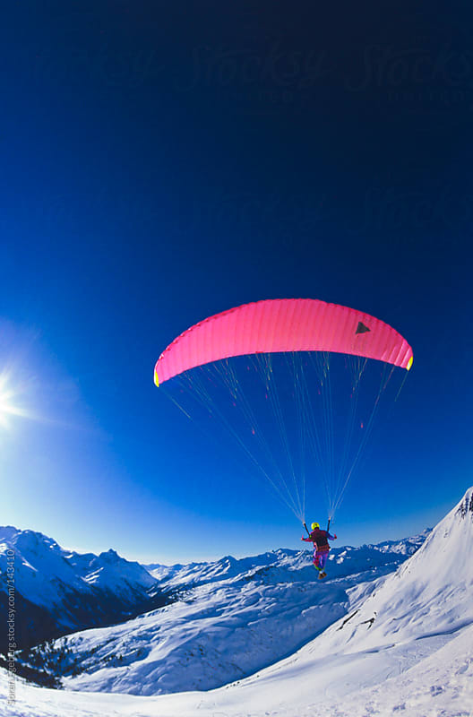Man paragliding in winter mountains with snow in St Anton am Arl by Soren Egeberg for Stocksy United