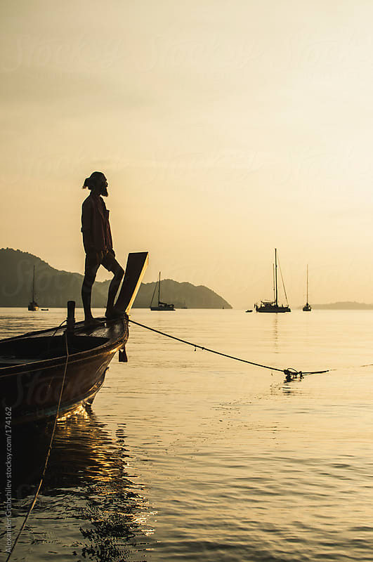 Man Sunset Silhouette On The Bow Of Boat by Alexander Grabchilev for Stocksy United