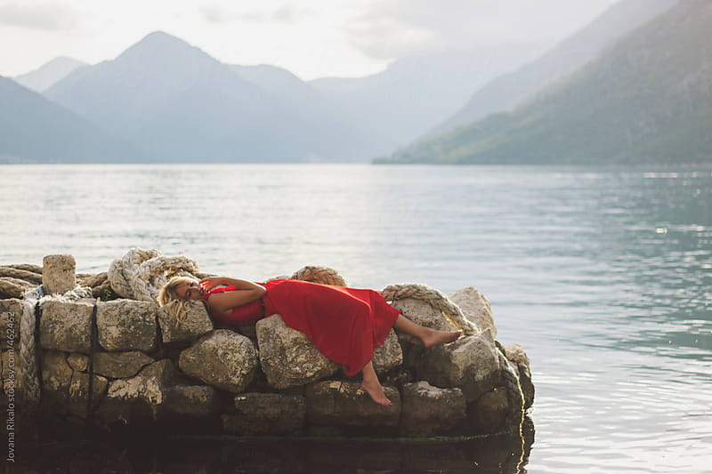 Young woman lies down on a dock by Jovana Rikalo for Stocksy United