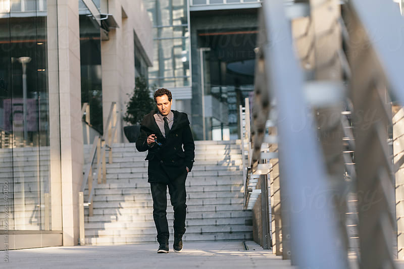 Young businessman walking in the Financial District by Davide Illini for Stocksy United