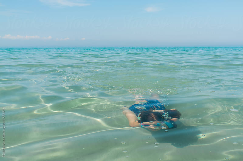 Girl swimming underwater in a lake or ocean. by Melissa Ross for Stocksy United