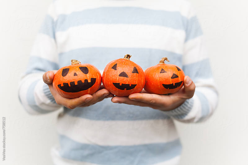 Man hands holding three small Halloween pumpkins  by Marija Mandic for Stocksy United