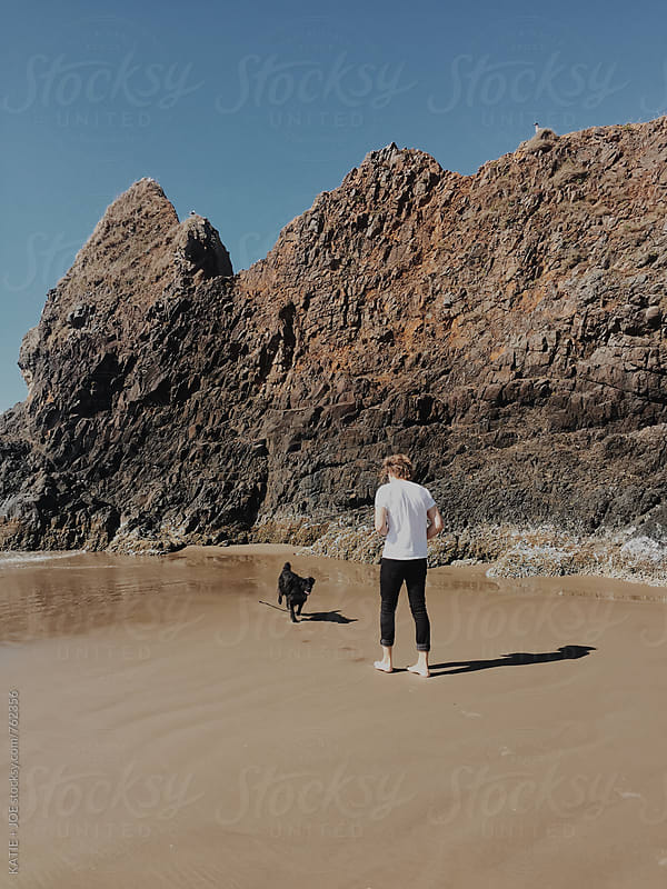 Man and a black dog on a rocky beach by KATIE + JOE for Stocksy United
