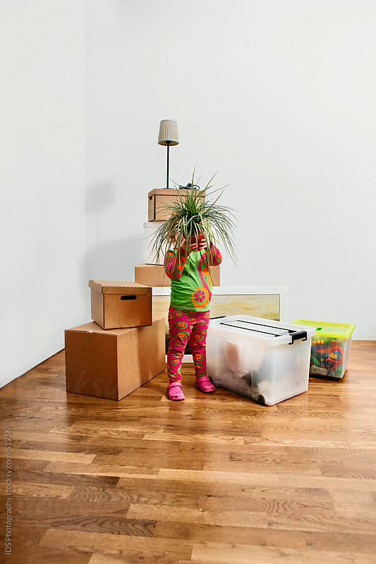 Young girl holding a plant in her new home by IDS Photography for Stocksy United