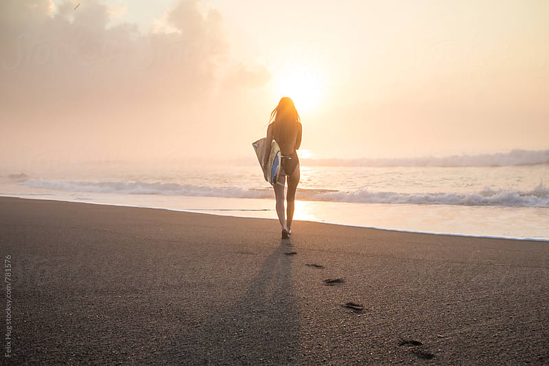 a young woman is walking towards the ocean with her surfboard by Felix Hug for Stocksy United
