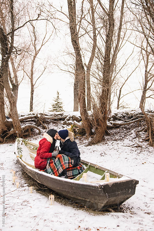 Photo of couple kissing in snowed boat by Danil Nevsky for Stocksy United
