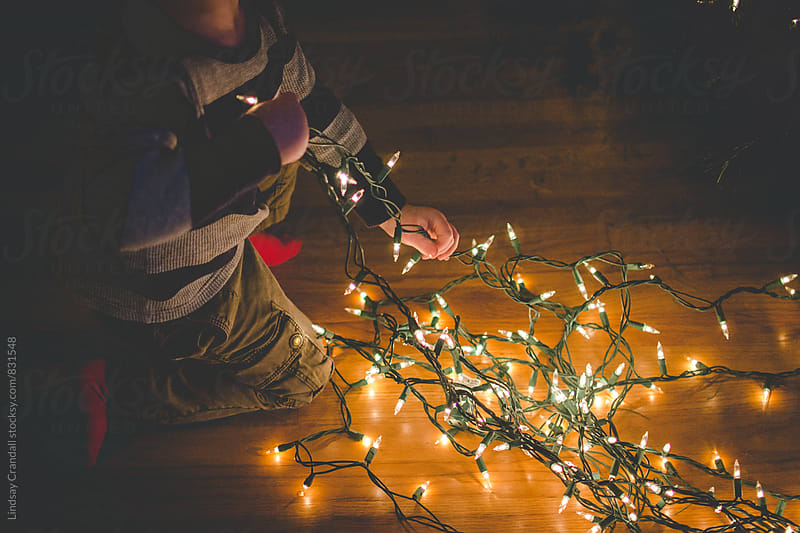 Child playing with Christmas string lights by Lindsay Crandall for Stocksy United