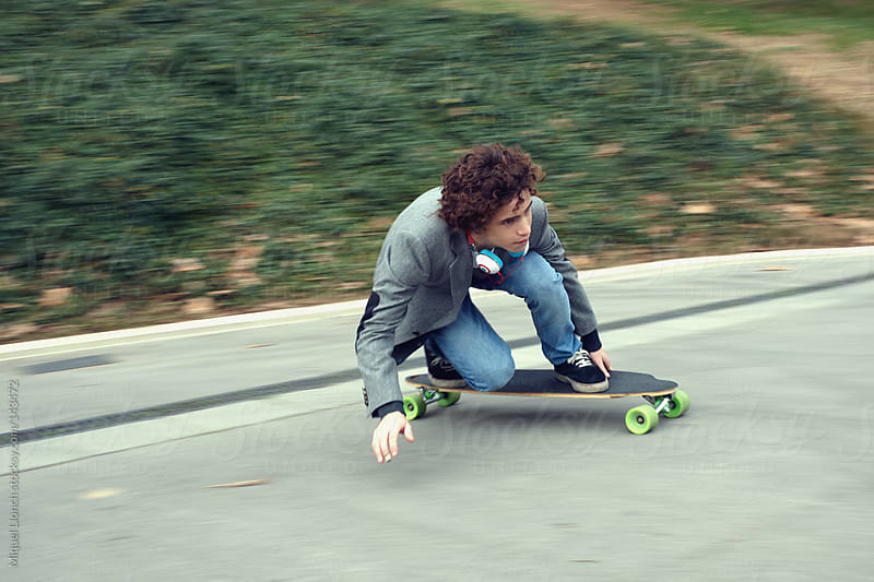 Teenager riding longboard by Miquel Llonch for Stocksy United