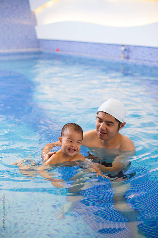 young man teach his baby boy swimming in swimming pool indoor by Bo Bo for Stocksy United