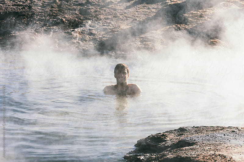 Young man bathing in natural hot springs water with steam by Alejandro Moreno de Carlos for Stocksy United