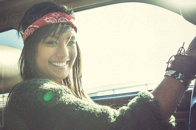 Smiling young Asian woman driving a car by Suprijono Suharjoto for Stocksy United