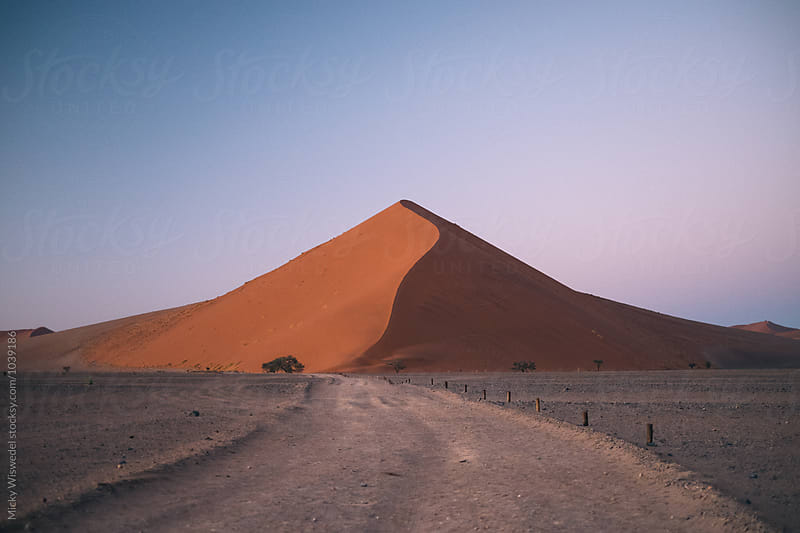 Dirt track leading to giant sand dune at dawn by Micky Wiswedel for Stocksy United