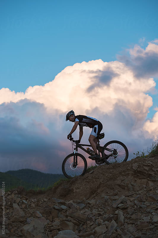 Young cyclist riding downhill by RG&B Images for Stocksy United