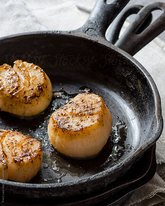 Fresh golden scallops on frying pan by Trent Lanz for Stocksy United