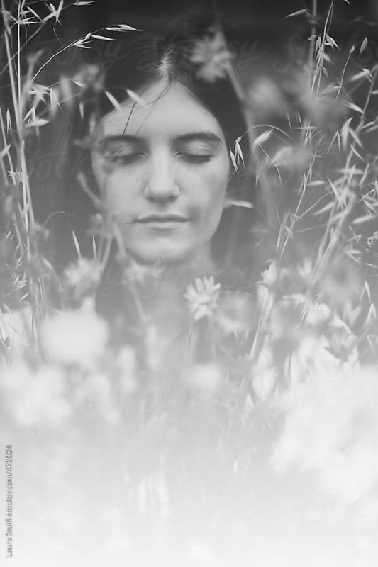 Black and white ethereal portrait of woman with eyes closed amongst wildflowers in bloom by Laura Stolfi for Stocksy United