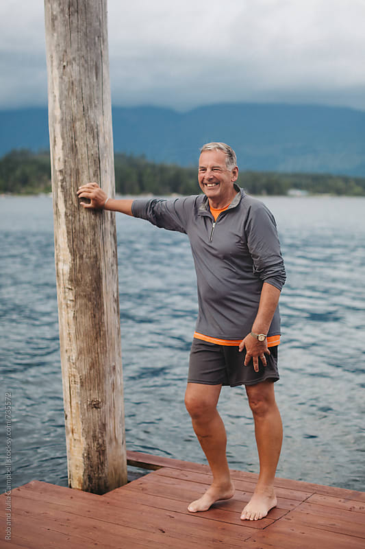 Portrait of older man smiling near water - leaning on dock pole by Rob and Julia Campbell for Stocksy United