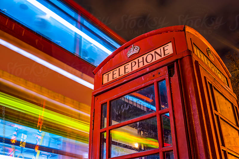 Telephone box and blurred bus in London by GIC for Stocksy United