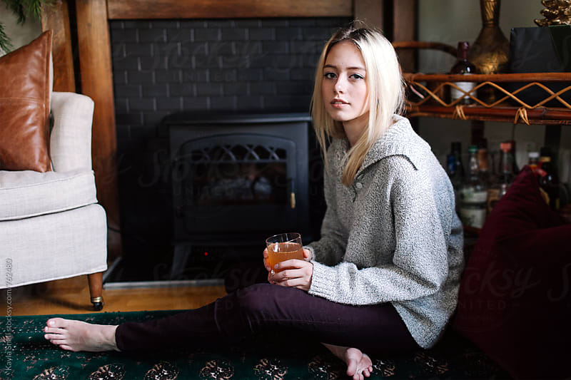 Woman drinking by the fire by Kayla Snell for Stocksy United