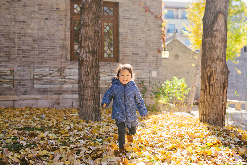 Cheerful toddler girl running in a park on a sunny autumn day by Maa Hoo for Stocksy United