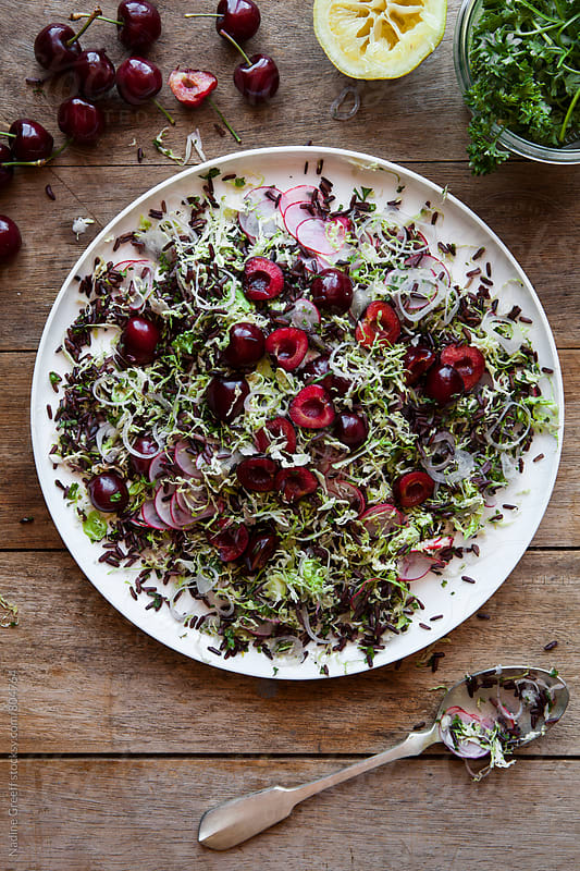 Plate of black rice, brussel sprout, red cherry salad side dish by Nadine Greeff for Stocksy United