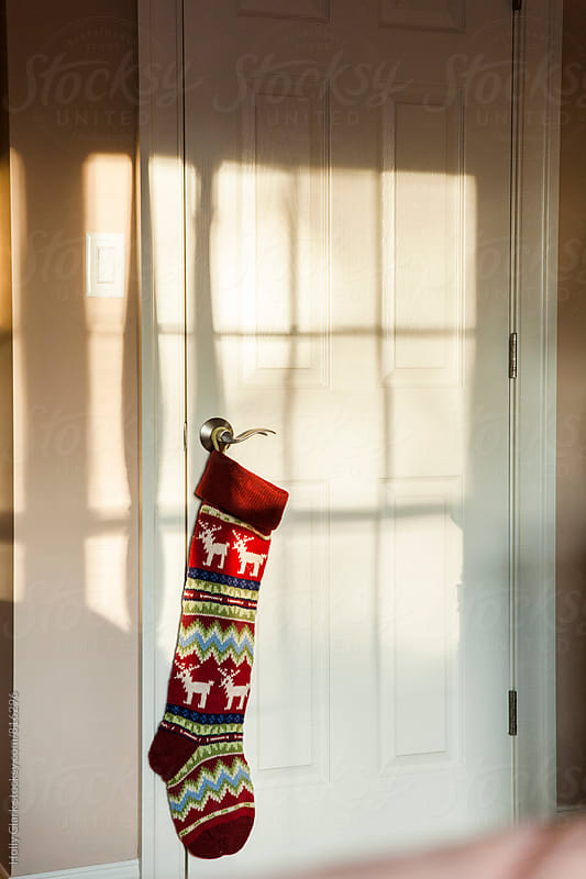 Chirstmas stocking hanging from doorknob by Holly Clark for Stocksy United