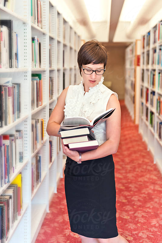in the library, studious woman by Gillian Vann for Stocksy United