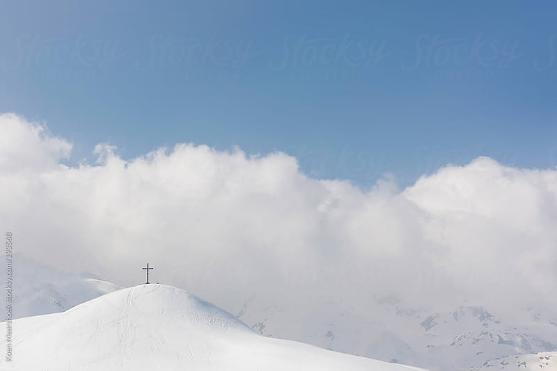 A cross on the top of a snowy mountain. by Koen Meershoek for Stocksy United