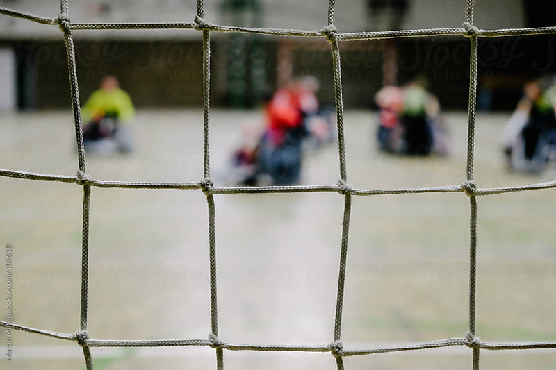 Net with defocused wheelchair rugby players in the background by Martin Matej for Stocksy United