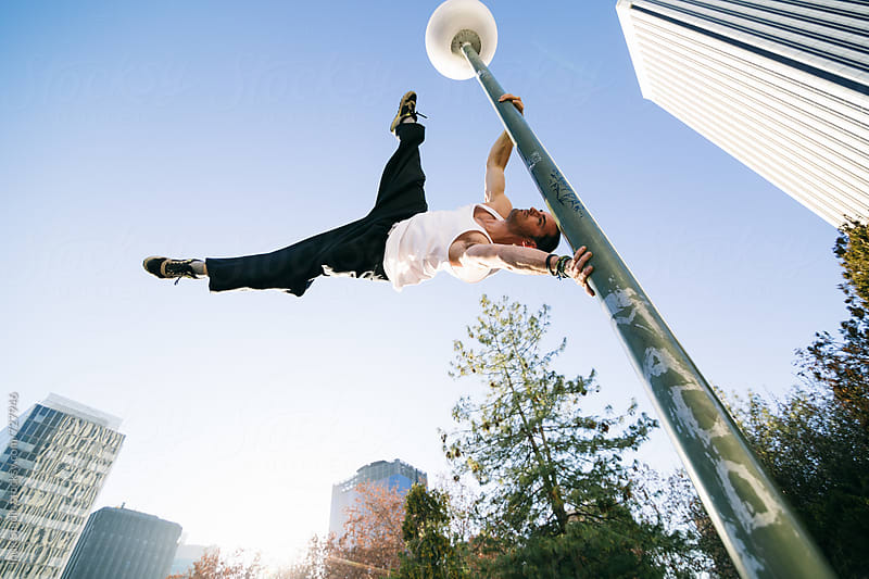 Man holding on to lamp post doing the human flag trick during a parkour session by Inuk Studio for Stocksy United