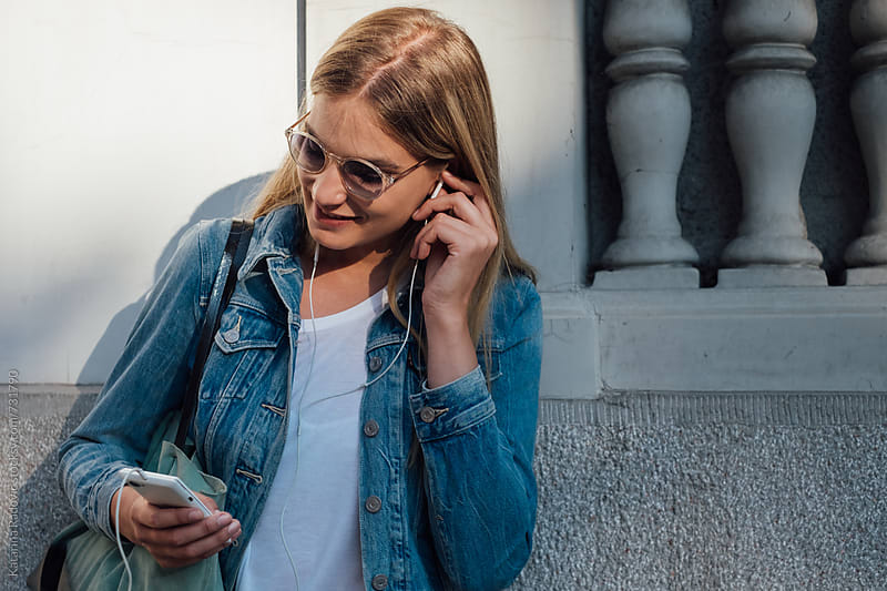 Pretty Blonde Woman Using Phone and Headphones  by Katarina Radovic for Stocksy United