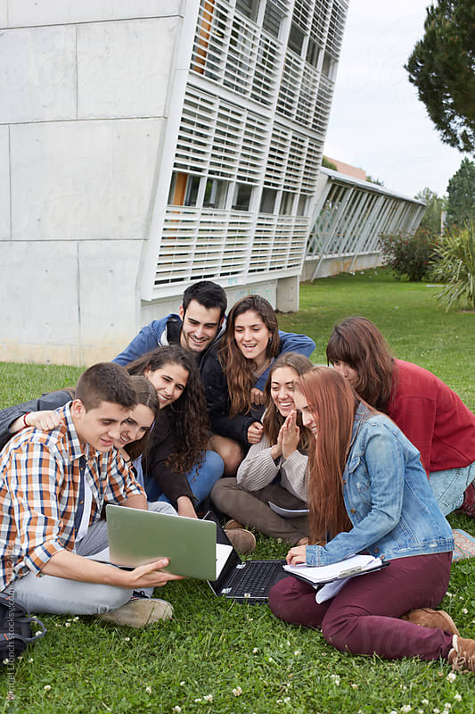 Group of young people in a happy moment at the campus by Miquel Llonch for Stocksy United