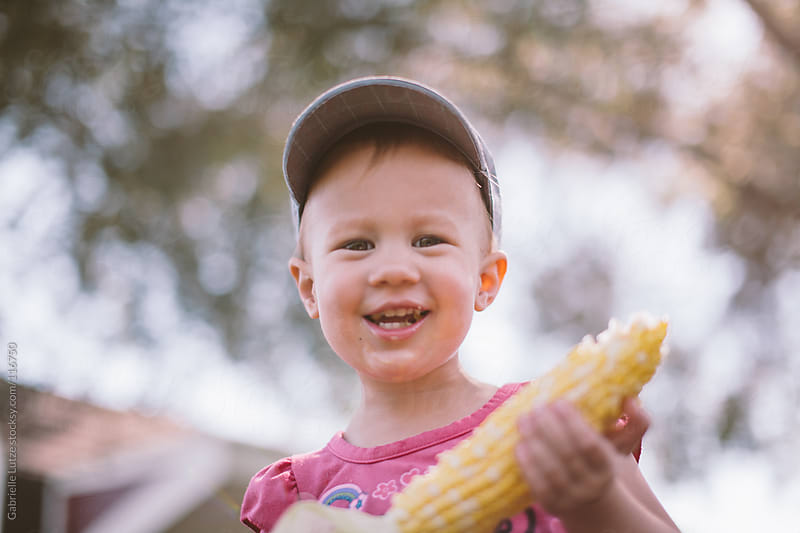 Little Girl Eating Corn by Gabrielle Lutze for Stocksy United