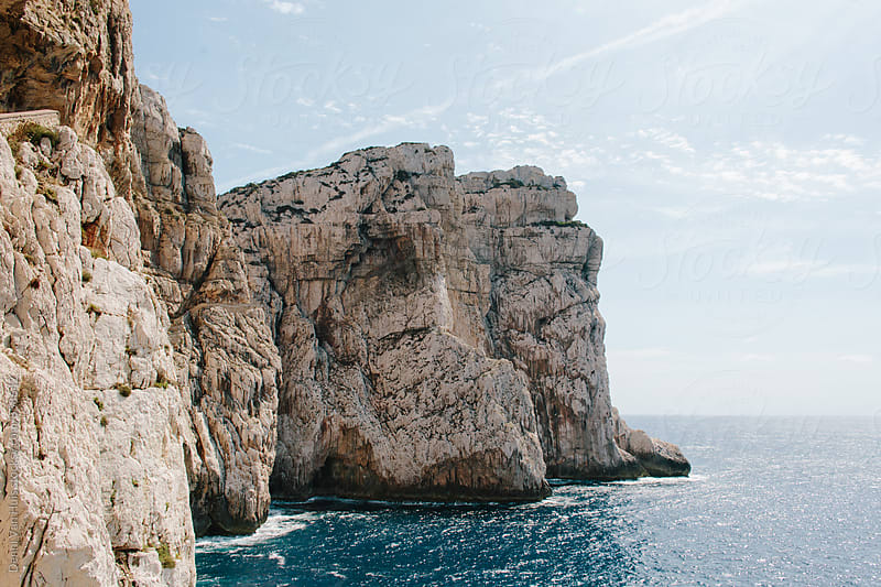 Rocky cliffs along a ocean by Denni Van Huis for Stocksy United