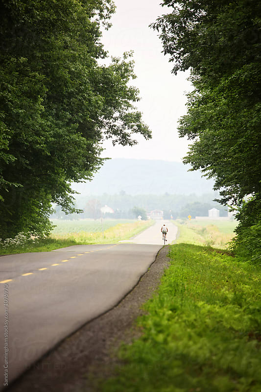 Rural country road with man cycling  by Sandra Cunningham for Stocksy United