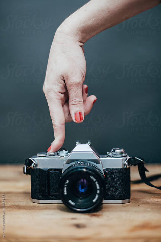 Hand pushing the button of a camera by Vera Lair for Stocksy United