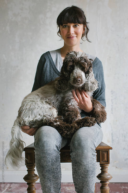 Portrait of Pretty Woman Sitting on Chair Holding Her Cocker Spaniel by Julien L. Balmer for Stocksy United