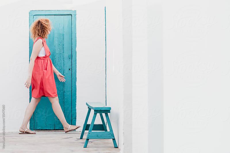 Side view of woman in orange dress walking against of blue door by Vera Lair for Stocksy United