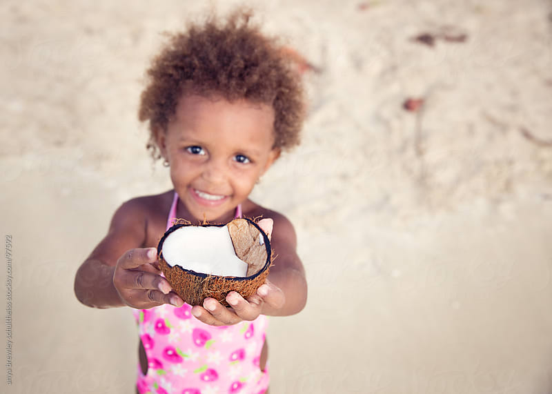 Young girl holding a cracked open coconut by anya brewley schultheiss for Stocksy United
